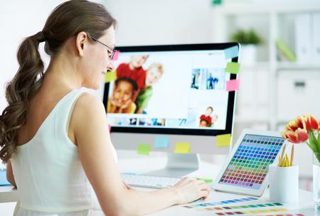 Vrouw werkt aan de computer en riskeert rugpijn door foute zithouding aan de tafel