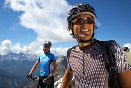 Manner rijden met hun fiets in de bergen om rugpijn te voorkomen