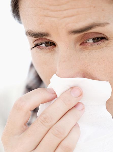 Vrouw snuit haar neus bij een verkoudheid