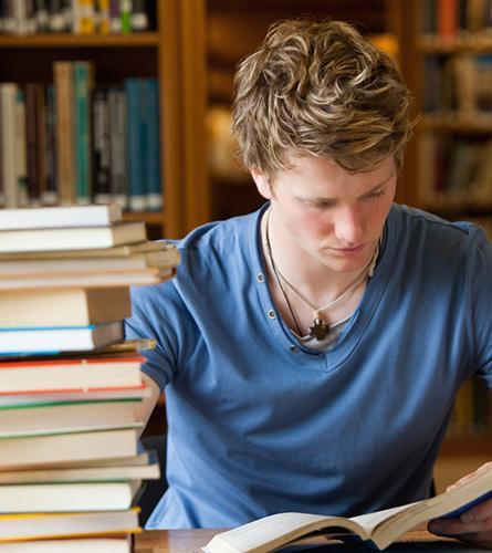 Jonge man studeert en lijdt onder spanningspijn door stress en foute belastingen van de spieren.